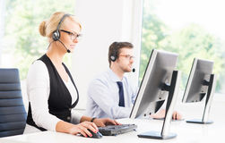 Customer support operators in formalwear working using computers Stock Photos