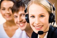 Customer Support Representative. Pretty Customer Support Representative  with a smile on the background of people Stock Photos