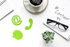 Customer support service desktop with contact us signs on white background top view. Customer support service desktop with contact us signs on white office Royalty Free Stock Photos