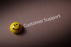 Customer support. And smiley icon isolated on brown background stock photo