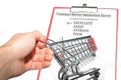 Customer survey. Customer service survey concept with clipboard and hand holding shopping cart Royalty Free Stock Image