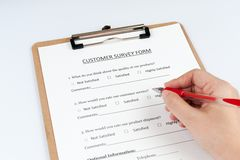 Customer survey form. FIlling customer survey form using a red pen royalty free stock photos