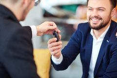 Customer takes the keys to the car from salesman of cars stock images