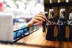 Customer taking bottle of beer from shelf in liquor store. Woman shopping alcohol or supermarket staff filling and stocking. royalty free stock photo