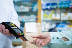 Customer taking credit card from payment terminal. In pharmacy royalty free stock images
