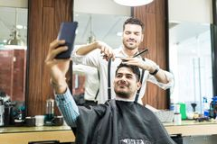 Customer Taking Selfie On Phone While Barber Styling His Hair royalty free stock photos