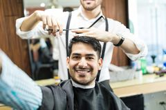 Customer Taking Selfie While Stylist Cutting His Hair With Sciss. Happy male customer taking selfie while stylist cutting his hair with scissors in shop Royalty Free Stock Photo