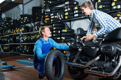 Customer talking with technician. Male customer talking with technician about motorcycle tires in work shop Stock Images