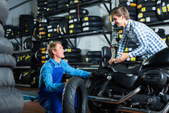 Customer talking with technician. Young men customer chatting with technician about motorcycle tires in work shop Royalty Free Stock Photo