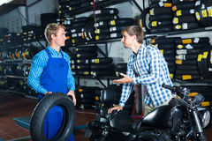 Customer talking with technician. Young men customer talking with technician about motorcycle tires in service shop Royalty Free Stock Images