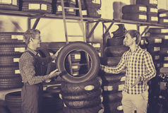 Customer talking with technician. Young men customer talking with technician about motorcycle tires in work shop Stock Images
