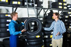 Customer talking with technician. Young men customer talking with technician about motorcycle tires in work shop Royalty Free Stock Image