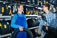 Customer talking with technician. Young men customer standing and talking with technician about motorcycle tires in work shop Stock Photo