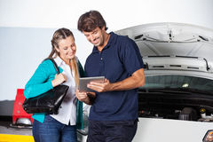 Customer And Technician Using Digital Tablet By Car royalty free stock photos