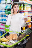 Customer telephoning to consult. Glad young girl customer telephoning to consult about shopping in supermarket Royalty Free Stock Photos