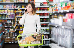 Customer telephoning to consult. Glad young customer telephoning to consult about shopping in supermarket Royalty Free Stock Photos