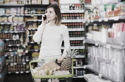 Customer telephoning to consult. Glad young customer telephoning to consult about shopping in supermarket Stock Image