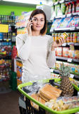 Customer telephoning to consult. Happy girl customer telephoning to consult about shopping in supermarket Royalty Free Stock Photography