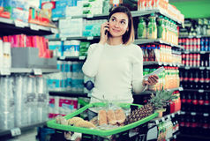 Customer telephoning to consult. Happy customer telephoning to consult about shopping in supermarket Stock Images