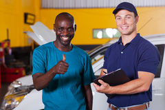 Customer thumb up. Happy african customer giving thumb up in car repair shop Royalty Free Stock Images