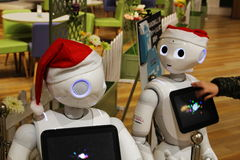 Customer touches the tablet attached to a santa-hat-clad Pepper robot in a Japanese shopping Mall Royalty Free Stock Photo