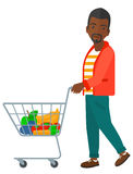 Customer with trolley. An african-american man pushing a supermarket cart with some goods in it vector flat design illustration isolated on white background stock illustration