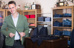 Customer is trying on new emerald jacket. In male clothes store Stock Photography