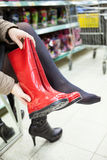 Customer trying red rubber boots in shop hall Stock Photos