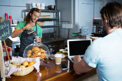 Customer using laptop at counter while staff preparing coffee. In coffee shop Stock Images