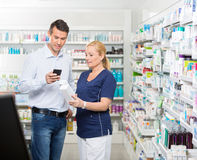 Customer Using Mobile Phone While Chemist Holding Royalty Free Stock Photo