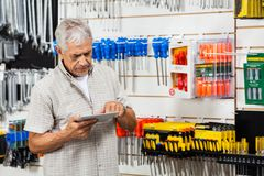 Customer Using Tablet Computer In Hardware Shop Stock Image