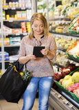 Customer Using Tablet Computer While Shopping In Grocery Store Stock Image