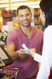 Customer Using Vouchers At Supermarket Checkout stock photography
