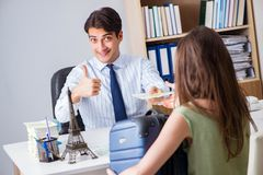 The customer visiting travel agency and talking to agent. Customer visiting travel agency and talking to agent Stock Photo