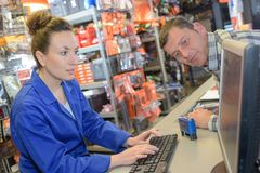 Free Customer Watching Sales Clerk On Computer Royalty Free Stock Photography - 123022617