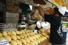 Customer weighs mangoes Royalty Free Stock Photos
