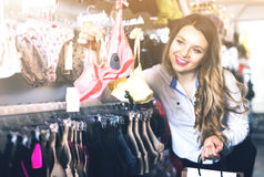 Customer woman in lingerie shop. Young attractive woman choosing pretty bra in lingerie store Stock Images