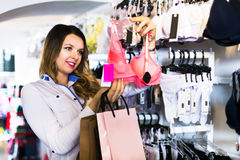 Customer woman in lingerie shop. Young female customer choosing pretty bra in underwear store Royalty Free Stock Images
