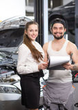 Customer woman and mechanic. Portrait of happy customer women standing on background of repaired car or automobile with mechanic men who solved all problems with Royalty Free Stock Photography