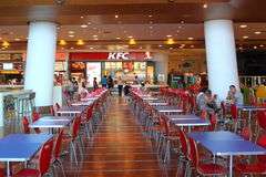 Customers buying fast food at KFC. Customers are buying fast food products inside a KFC (Kentucky Fried Chicken) restaurant.Blue tables and red chairs Royalty Free Stock Image