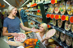 Customers buying frozen pizza in shop. Smiling female pensioner and daughter buying frozen pizza in shop Stock Image