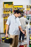 Customers Buying Tools In Store. Male customers buying tools in hardware store Stock Image