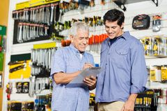 Customers Checking Checklist In Hardware Store. Smiling father and son checking checklist on clipboard while standing in hardware store Stock Image