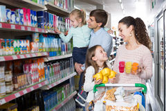 Customers with children selecting sweet dairy products in hyper. Happy ordinary  customers with children selecting sweet dairy products in hypermarket Royalty Free Stock Image