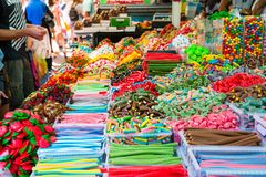 Customers choose sweets from counter with assorted colorful different shape jelly candies on market place in Tel Aviv, Israel. Sel. Ective focus, space for text royalty free stock photography