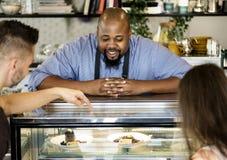 Customers choosing cake at the display fridge royalty free stock photos
