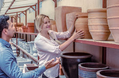Customers choosing crockery. Male and positive young women customers choosing crockery in ceramics workshop royalty free stock photography