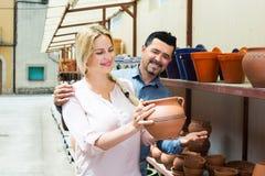 Customers choosing crockery. Positive male and young female customers choosing crockery in ceramics workshop stock image