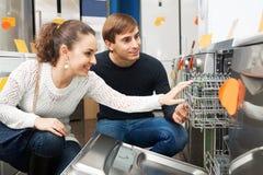 Customers choosing new dish washing machine. Ordinary young customers choosing new dish washing machine in supermarket royalty free stock image