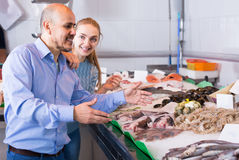 Customers choosing seafood in fish store and smiling Stock Photo